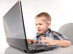 Computer addiction emotional boy with laptop Stock Photos