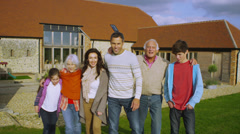 Portrait of happy extended family group standing outside rural home Stock Footage