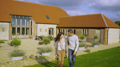 Portrait of happy attractive couple standing outside rural home Stock Footage
