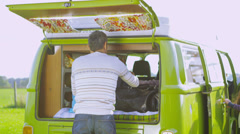 Happy family packing the camper van and going on holiday - stock footage