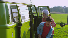 Happy affectionate family with camper van taking a holiday in the countryside - stock footage