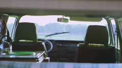 Attractive couple in camper van lean over to share a kiss - stock footage