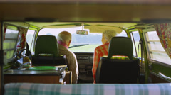 Attractive mature couple in camper van lean over to share a kiss - stock footage