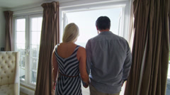 Romantic couple go to look at the view from balcony of their beachside apartment Stock Footage
