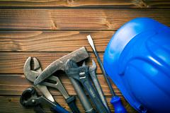 Hard hat with various working tools Stock Photos