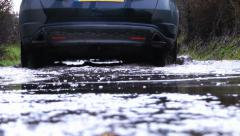 Driving shot - A car drives through flooded road Stock Footage