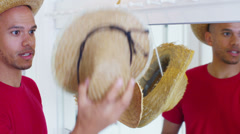 Young happy couple have fun trying on a selection of straw hats. - stock footage
