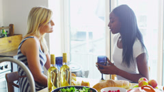 Young female friends drinking wine together and having a conversation - stock footage