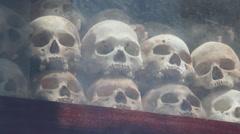 MCU swish pan across skulls on display in Killing Fields memorial, Cambodia Stock Footage