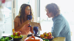 Couple relaxing together at home with newspaper and glass of wine - stock footage