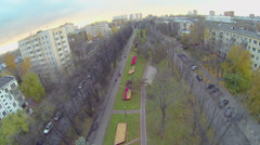 Citizens walk by boulevard with flowerbeds and car traffic Stock Footage
