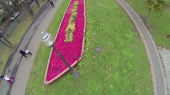 People walk by path near colorful flowerbed at autumn day Stock Footage