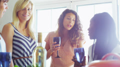 Cheerful group of female friends drinking wine and gossiping - stock footage