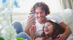 Attractive young couple relaxing together at home and looking at a smartphone - stock footage