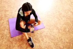 young fit woman sitting on the yoga mat and holding bottle with water at gym - stock photo