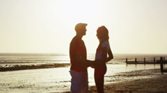 Romantic couple holding hands and walking on the beach at sunset - stock footage