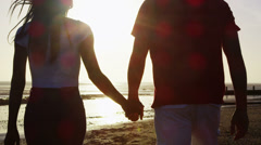 Romantic couple holding hands and walking on the beach at sunset Stock Footage