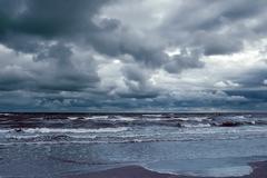 Iso valtameren aallot rikkovat rannalla ja tumma myrskyinen taivas Kuvituskuvat