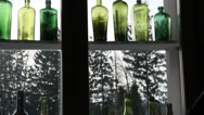 Different kinds of colored bottles on the window Stock Footage