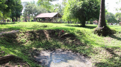 Tilt down to mass grave at Killing Fields, Cambodia Stock Footage