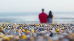 Romantic couple sitting on the beach on a summer evening Stock Footage