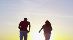 Romantic couple running on the beach at sunset Stock Footage