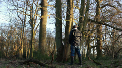 Man relieves himself in the woods Stock Footage