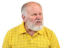 Disgusted displeased senior bald man in yellow shirt Stock Photos
