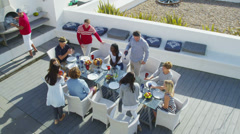 Happy group of family and friends enjoy a meal outdoors at luxury beachside home - stock footage