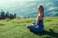 Stock Photo of young woman meditating outdoors