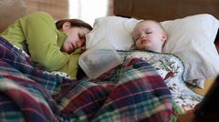 Toddler with flu lying next to mother Stock Footage