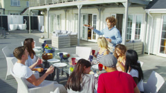 Happy group of family and friends enjoy a meal outdoors at luxury beachside home Stock Footage