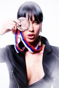 Stock Photo of beautiful stylish woman holding a medal