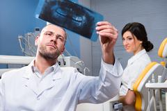 dentist with x-ray and smiling patient in the background - stock photo