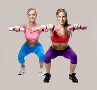 two beautiful young woman doing fitness exercise with dumbbells - stock photo