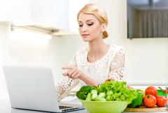 young woman looking for a recipe on the laptop computer in the kitchen - stock photo