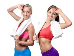 Two beautiful girls after workout with towels on white background Stock Photos