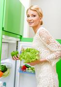 smiling young woman taking vegetables out of fridge - stock photo