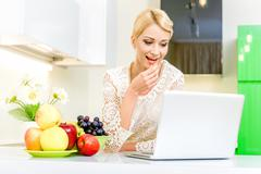 Beautiful young woman using her laptop computer in the kitchen Stock Photos