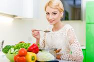 Stock Photo of young woman tasting soup