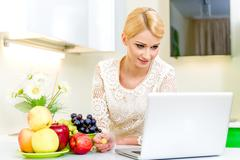 Young woman looking for a recipe on the laptop computer in the kitchen Stock Photos