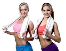 two beautiful girls after workout with towels on white background - stock photo