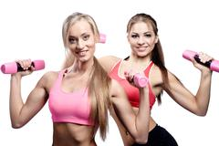 Two beautiful young woman doing fitness exercise with dumbbells Stock Photos