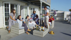 Casual group of friends socializing with drinks outside beachside home Stock Footage