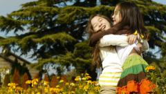 Cute Asian Sisters Playing And Hugging In A Flower Garden Stock Footage
