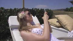 SLOW MOTION: Young woman using a smartphone poolside Stock Footage