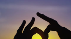 Hands join together to make a heart shape, outdoors on a beach at sunset Stock Footage