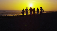 Carefree group of friends running on the beach at sunset - stock footage