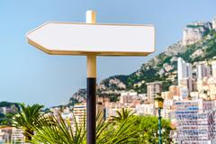 signpost and beautiful panoramic view of monaco on background - stock photo