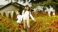 Adorable Sisters Walking Through A Marigold Garden Holding Hands Stock Footage